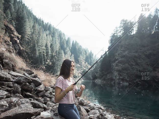 Woman fishing in lake, Antronapiana, Piemonte, Italy