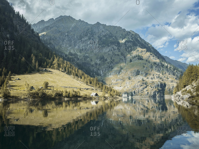 Cloudscape over mountain ranges reflected in lake, Antronapiana, Piemonte, Italy