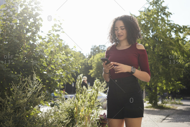 Young woman using cellphone in park, Berlin, Germany