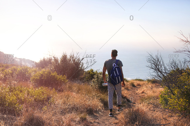 Young male hiker walking toward sea cliff, rear view, Cape Town, Western Cape, South Africa