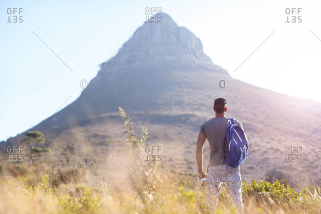 Young male hiker looking at mountain in Table Mountain National Park, rear view, Cape Town, Western Cape, South Africa