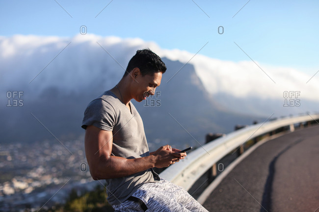 Young male runner sitting on rural road barrier looking at smartphone, Cape Town, Western Cape, South Africa