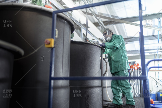 Worker at mixing tanks in chemical factory