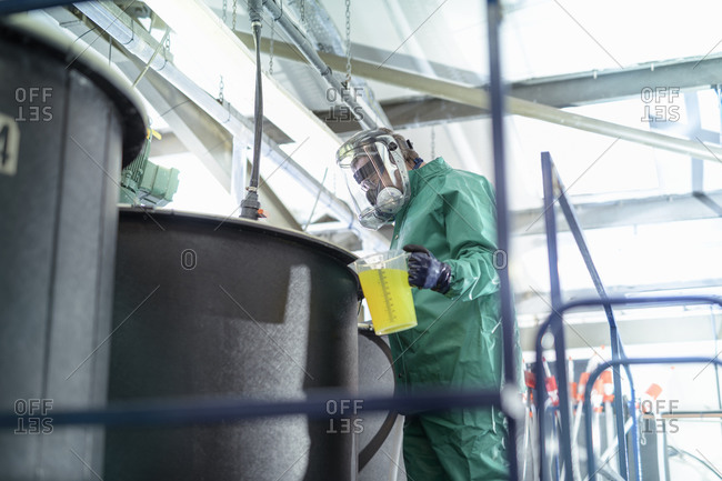 Worker pouring chemical into mixing tanks in chemical factory