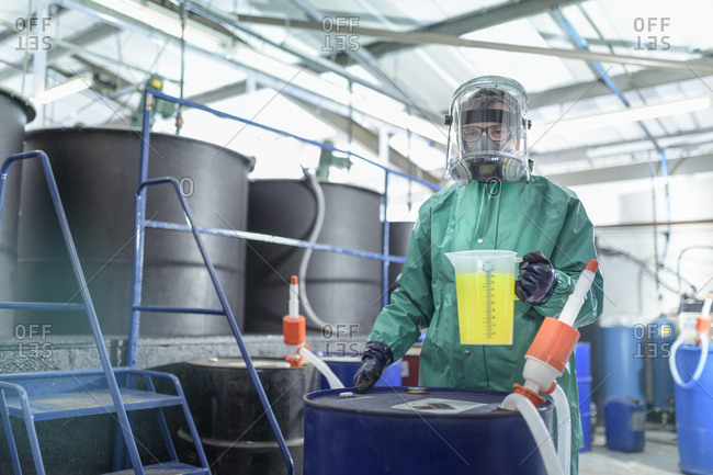 Worker with jug of chemical in chemical factory