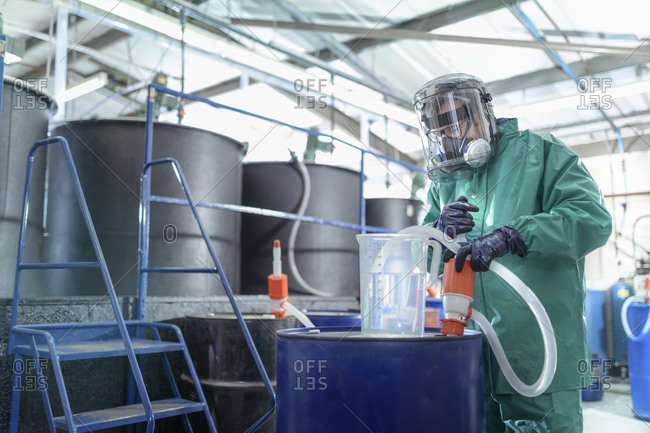 Worker filling jug with chemical in chemical factory