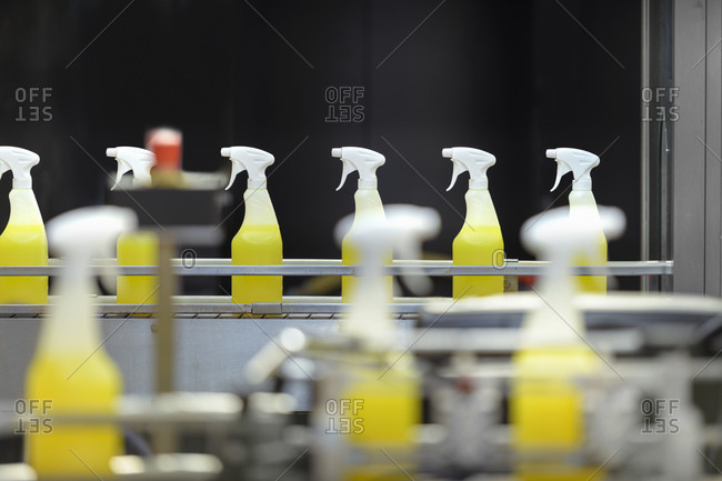 Spray bottles on filling line in chemical factory
