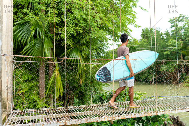 Man with surfboard on rope bridge, Pagudpud, Ilocos Norte, Philippines