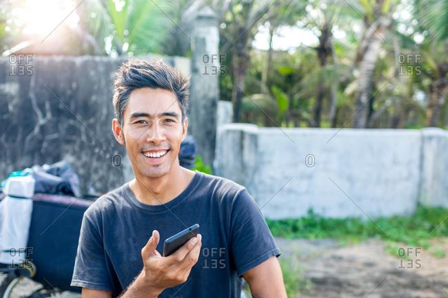 Man using cellphone on road trip, Pagudpud, Ilocos Norte, Philippines
