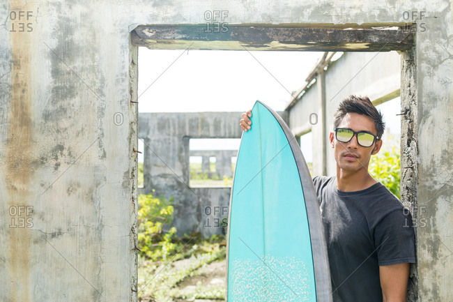 Surfer by doorway of abandoned building, Abulug, Cagayan, Philippines