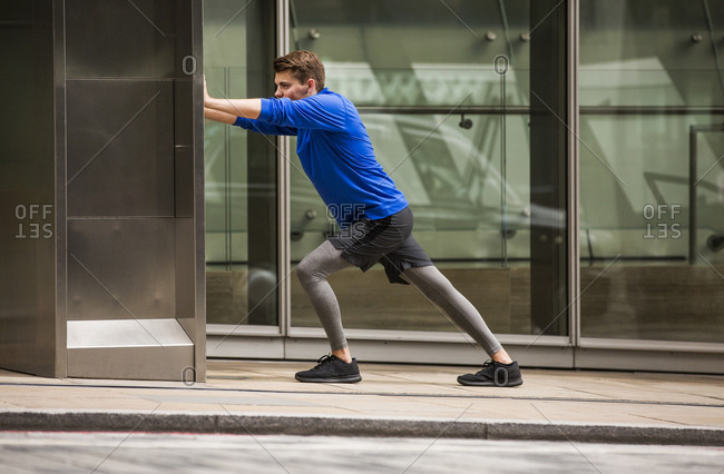 Young runner stretching on pavement, London, UK