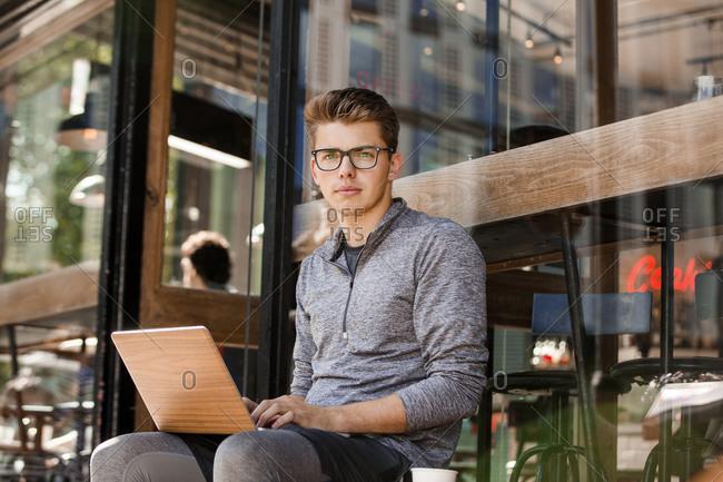 Young man using laptop at cafe, London, UK