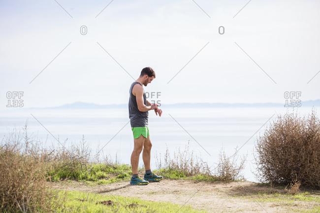 Runner checking time on cliff top, Santa Barbara, California, USA