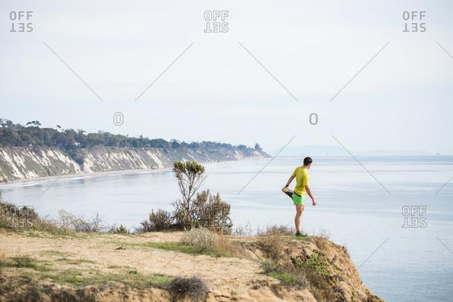 Runner stretching on cliff top, Santa Barbara, California, USA