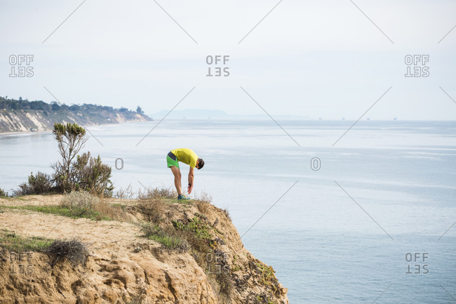 Runner stretching on cliff top, Santa Barbara, California, USA