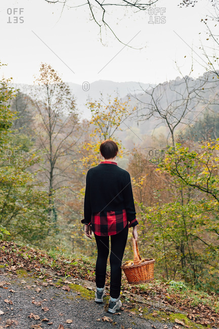 Woman with basket on hillside road, Rezzago, Lombardy, Italy