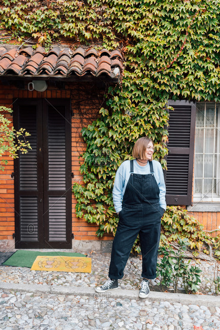Woman outside house with facade covered in ivy, Rezzago, Lombardy, Italy