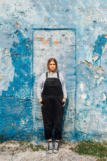 Portrait of woman, weathered wall in background