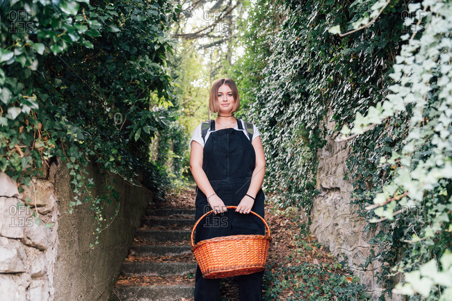 Woman with basket descending ivy-covered stairs