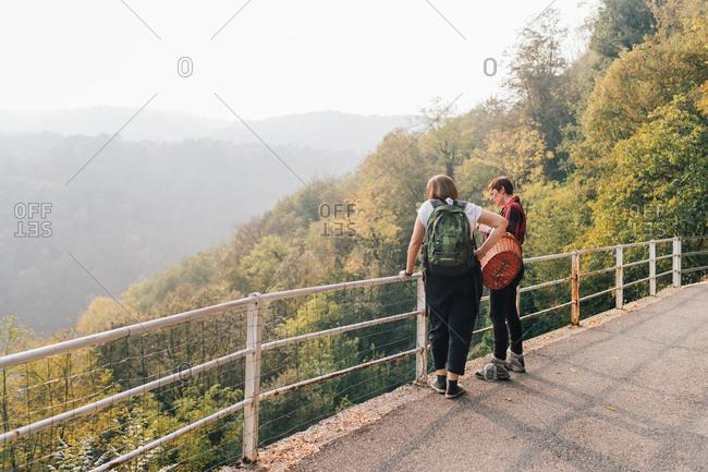 Friends on hillside road, Rezzago, Lombardy, Italy