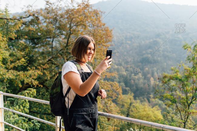 Woman taking photo on hillside, Rezzago, Lombardy, Italy