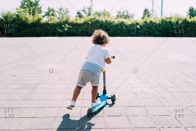 Toddler riding push scooter in park