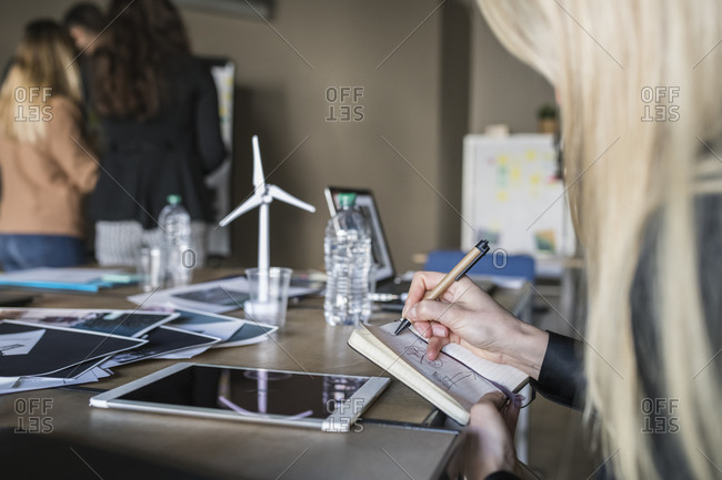 Businesswoman taking notes in office, colleagues in background