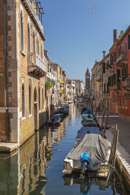 April 28, 2016: Moored boats on San Barnaba canal, footbridge and old architectural style residential buildings, church bell tower, Dorsoduro district, Venice, Veneto, Italy