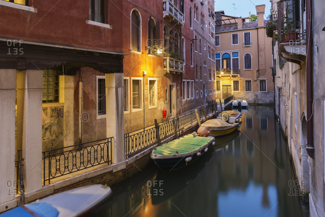 Illuminated Rio de Ca' Garzon Canal, moored boats and old architectural style residential buildings at dusk, San Marco district, Venice, Veneto, Italy