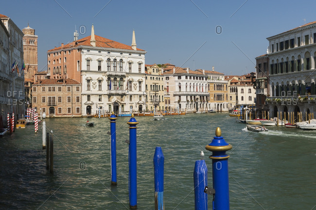 April 28, 2016: Blue mooring posts, water taxis on Grand Canal, Renaissance architectural style residential palace buildings, San Polo district, Venice, Veneto, Italy
