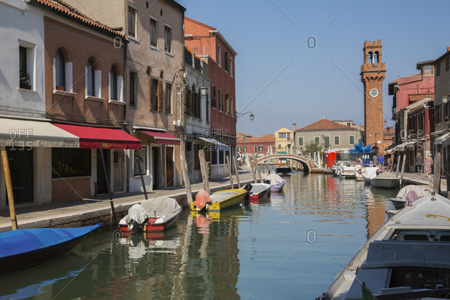 April 28, 2016: Moored boats on canal, colorful residential buildings, houses, shops and clock tower, San Stefano Square, Murano Island, Venetian Lagoon, Veneto, Italy