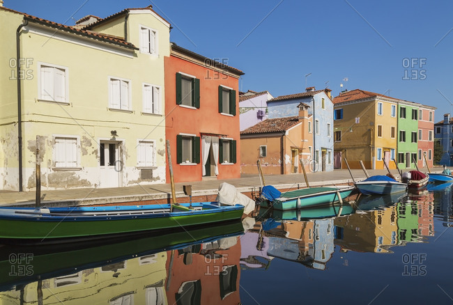 Moored green and blue boats on canal lined with colorful stucco houses, Burano Island, Venetian Lagoon, Venice, Veneto, Italy