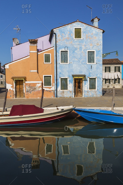 Moored boats on canal lined with orange, mauve and blue stucco houses, Burano Island, Venetian Lagoon, Venice, Veneto, Italy