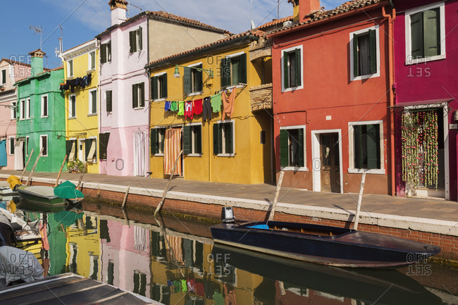 Moored boats on canal lined with pink, red, orange, yellow and green stucco houses decorated with curtains, washed clothes on clothesline, Burano Island, Venetian Lagoon, Veneto, Italy