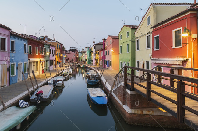 April 28, 2016: Moored boats on canal lined with colorful stucco houses, shops and footbridge at dusk, Burano Island, Venetian Lagoon, Venice, Veneto, Italy