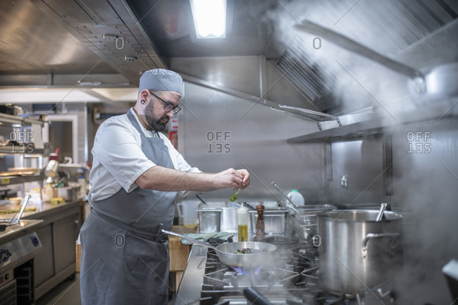 Chef putting herbs into pan in Italian restaurant kitchen