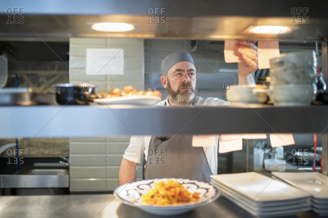 Chef reading order in Italian restaurant kitchen