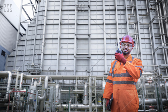 Composite image of worker using walkie talkie in power station