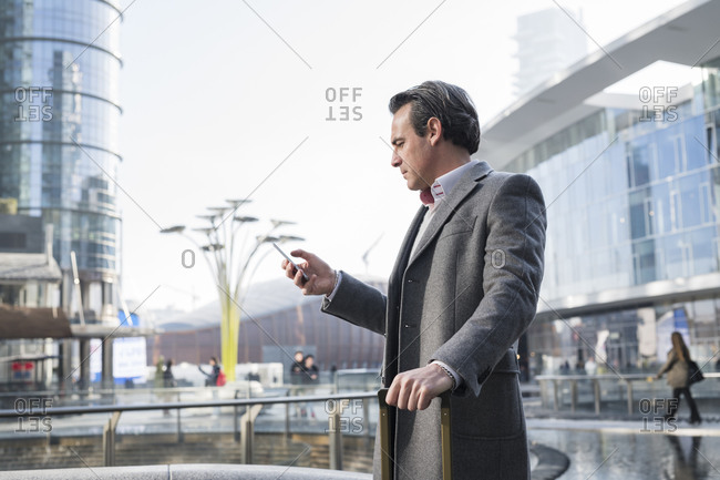 Businessman using smartphone in city center, Milan, Lombardia, Italy