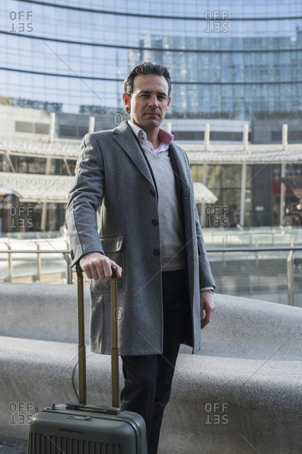 Businessman with wheeled luggage in city center, Milan, Lombardia, Italy
