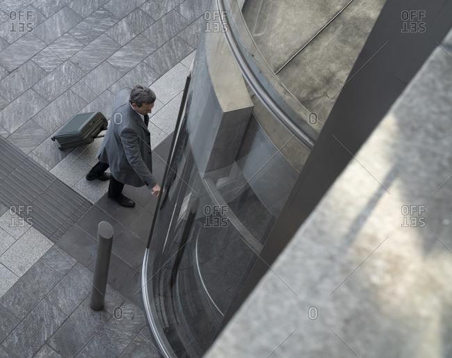 Businessman with wheeled luggage waiting for elevator