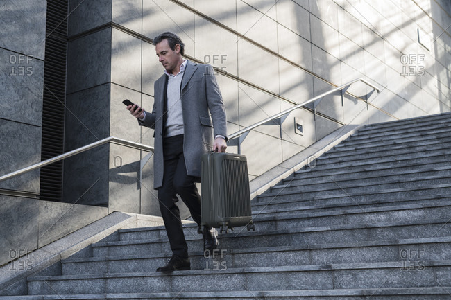 Businessman walking down stairway with wheeled luggage and using smartphone