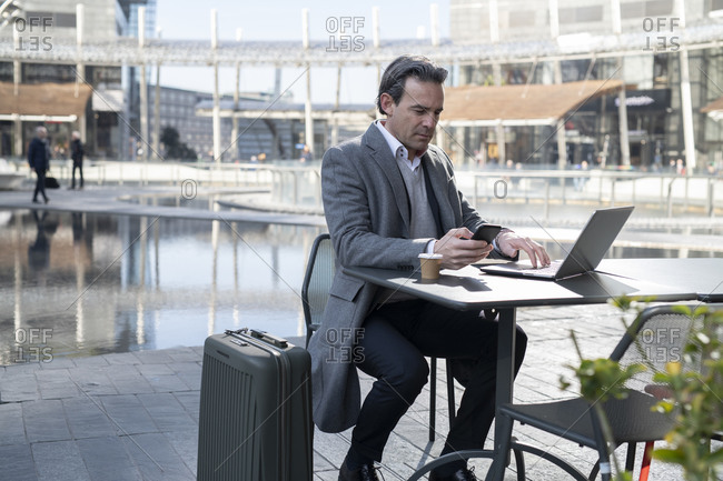 Businessman working on laptop in city center, Milan, Lombardia, Italy