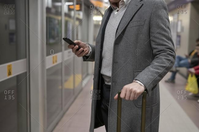 Businessman using smartphone on train platform