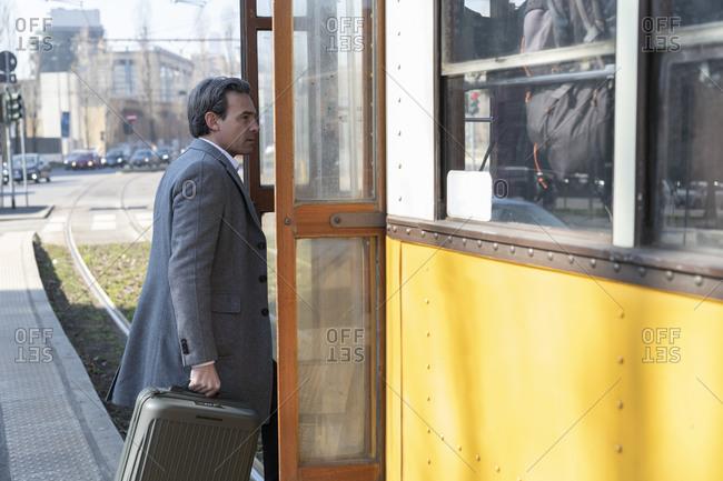 Businessman boarding tram with wheeled luggage