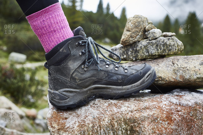 Female hiker stepping onto rock, close up of hiking boot