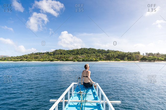 Woman sitting on bow of boat heading to island, Ginto island, Linapacan, Philippines