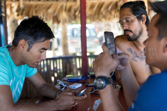 Friends using smartphone in beach hut, Pagudpud, Ilocos Norte, Philippines