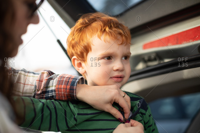 Boy getting fresh change of clothes at car boot