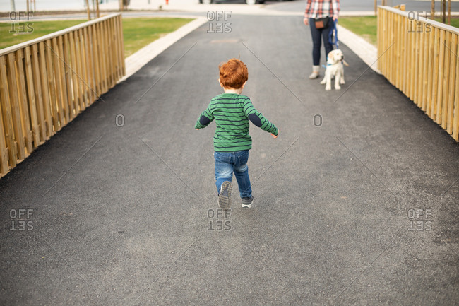 Boy running towards mother and pet puppy